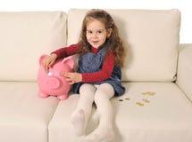 Gullig liten flicka som spelar med mynt och den enorma spargrisen på soffan Arkivfoto