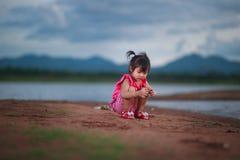 Gullig liten flicka som spelar på den härliga sjön Fotografering för Bildbyråer
