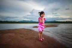 Gullig liten flicka som spelar på den härliga sjön Arkivfoton