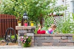 Gullig liten flicka som spelar på en trädgårds- vägg Royaltyfri Bild