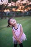 Gullig liten flicka som spelar på gräsvallen Royaltyfri Foto