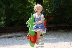 Gullig liten flicka som svänger på lekplatsen Arkivbild