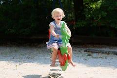 Gullig liten flicka som svänger på lekplatsen Arkivfoton