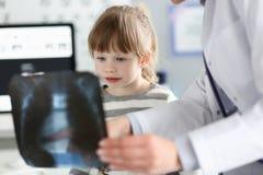 Gullig liten flicka som talar med gp som ser r?ntgenstr?lebilden under konsultation arkivfoto