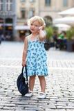 Gullig liten flicka som talar på mobiltelefonen i staden Arkivbild
