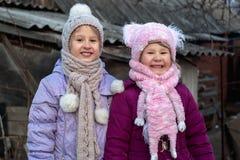 Gullig liten flicka som två poserar i byn i vinter fotografering för bildbyråer