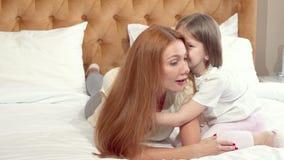 Gullig liten flicka som tycker om att vila hemma med hennes moder lager videofilmer