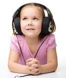 Gullig liten flicka som tycker om musik genom att använda hörlurar royaltyfria bilder