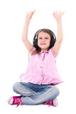 Gullig liten flicka som tycker om musik i hörlurar som isoleras på vit Royaltyfri Fotografi