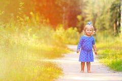 Gullig liten flicka som tycker om naturen som in spelar Royaltyfria Bilder