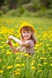 Gullig liten flicka som utomhus bär den blom- kransen royaltyfria foton