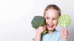 Gullig liten flicka som väljer mellan broccoli och sötsaker royaltyfria foton