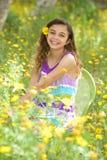 Gullig liten flicka utanför i ett blommafält Royaltyfri Foto