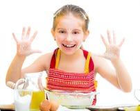 Gullig liten flickabakning på kök fotografering för bildbyråer