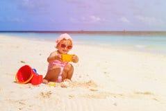 Gullig liten flickabyggnadssandslott på stranden Royaltyfri Bild