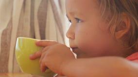 Gullig liten flickadrinkdryck från koppen på balkongen arkivfilmer