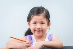 Gullig liten flickainnehavblyertspenna i hand Arkivbild
