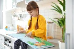 Gullig liten flickaläsebok i kök royaltyfri fotografi