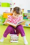 Gullig liten flickaläsning bokar sammanträde däckar på Arkivfoton