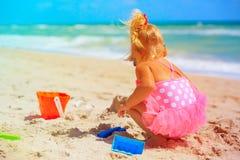 Gullig liten flickalek med sand på stranden arkivbilder