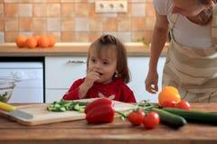 Gullig liten flickaprovningsgrönsak på köket arkivbilder