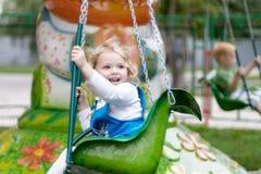 Gullig liten flickaridning på en karusell Arkivbilder