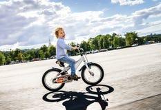 Gullig liten flickaridning som är snabb med cykeln Arkivbild