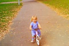 Gullig liten flickaridningrunbike i hösten, ungesport Arkivfoton