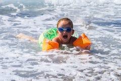 Gullig liten flickasimning i havet Arkivbild