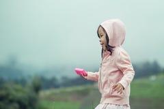 Gullig liten flickaspring för barn i trädgården efter regn Royaltyfri Fotografi