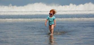 Gullig liten flickaspring i väg från havvågor på den Bali stranden Royaltyfri Bild