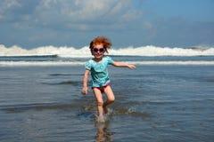 Gullig liten flickaspring i väg från havvågor på den Bali stranden Royaltyfri Foto