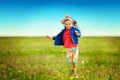 Gullig liten flickaspring på äng i ett fält Arkivfoto
