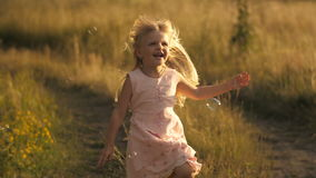 Gullig liten flickaspring på fältet stock video