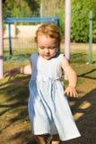 Gullig liten flickaspring på playgraund Arkivbild