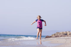 Gullig liten flickaspring på stranden Royaltyfri Fotografi
