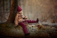 Gullig liten flickastående i en vårskog på den molniga dagen arkivfoto
