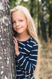 Gullig liten flickastående nära trädbjörk fotografering för bildbyråer
