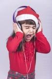 Gullig liten jultomtenflicka som lyssnar till musik Royaltyfri Bild
