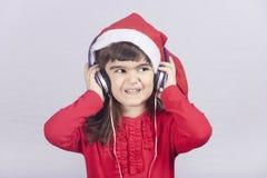 Gullig liten jultomtenflicka som lyssnar till musik Fotografering för Bildbyråer
