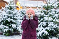 Gullig liten le ungeflicka på marknad för julträd Lyckligt barn i den vinterkläder och leksaken som väljer xmas-trädet på xmas arkivbilder
