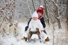 Gullig liten litet barnpojke och hans äldre bröder som utomhus spelar med snö på en vinterdag arkivbilder