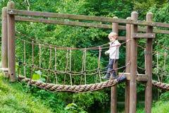 Gullig liten litet barnpojke som har gyckel med klättring på lekplats I Royaltyfri Foto