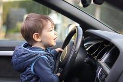 Gullig liten litet barnpojke som kör det stora hjulet för bilinnehavstyrning som framåtriktat ser på vindrutan arkivfoton