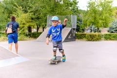 Gullig liten pojke som lär till skateboarden Arkivbild