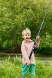 Gullig liten pojkeställning nära en flod med en metspö i hans händer Royaltyfria Bilder
