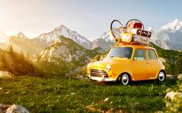 Gullig liten retro bil med resväskor och cykeln överst på gräsfält på berget i sommardag royaltyfri fotografi