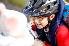 Gullig liten ridning för skolaungepojke på pushsparkcykeln på vägen till eller från skolan E arkivbild