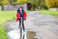 Gullig liten ridning för skolaungepojke på pushsparkcykeln på vägen till eller från skolan Skolpojke av 7 år som igenom kör arkivbild