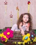 Gullig liten söt flicka i en påskgarnering hemma Arkivfoto
